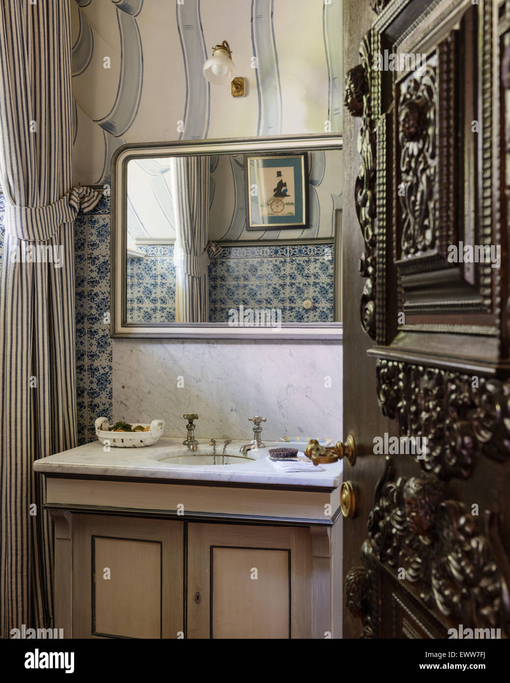 Marble topped vanity unit in cloakroom with tiled walls - Stock Image