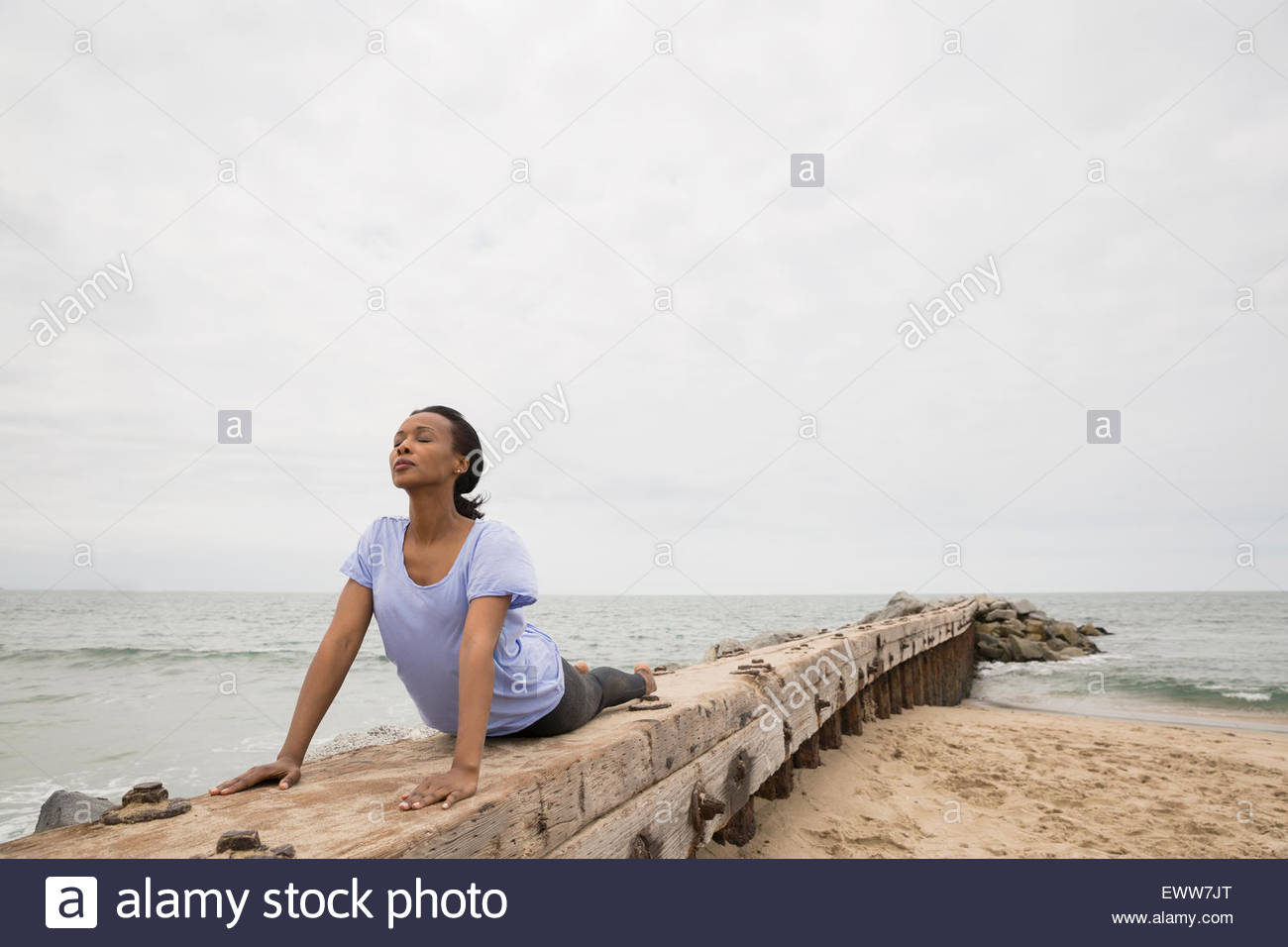 Serene woman in upward facing dog position beach - Stock Image