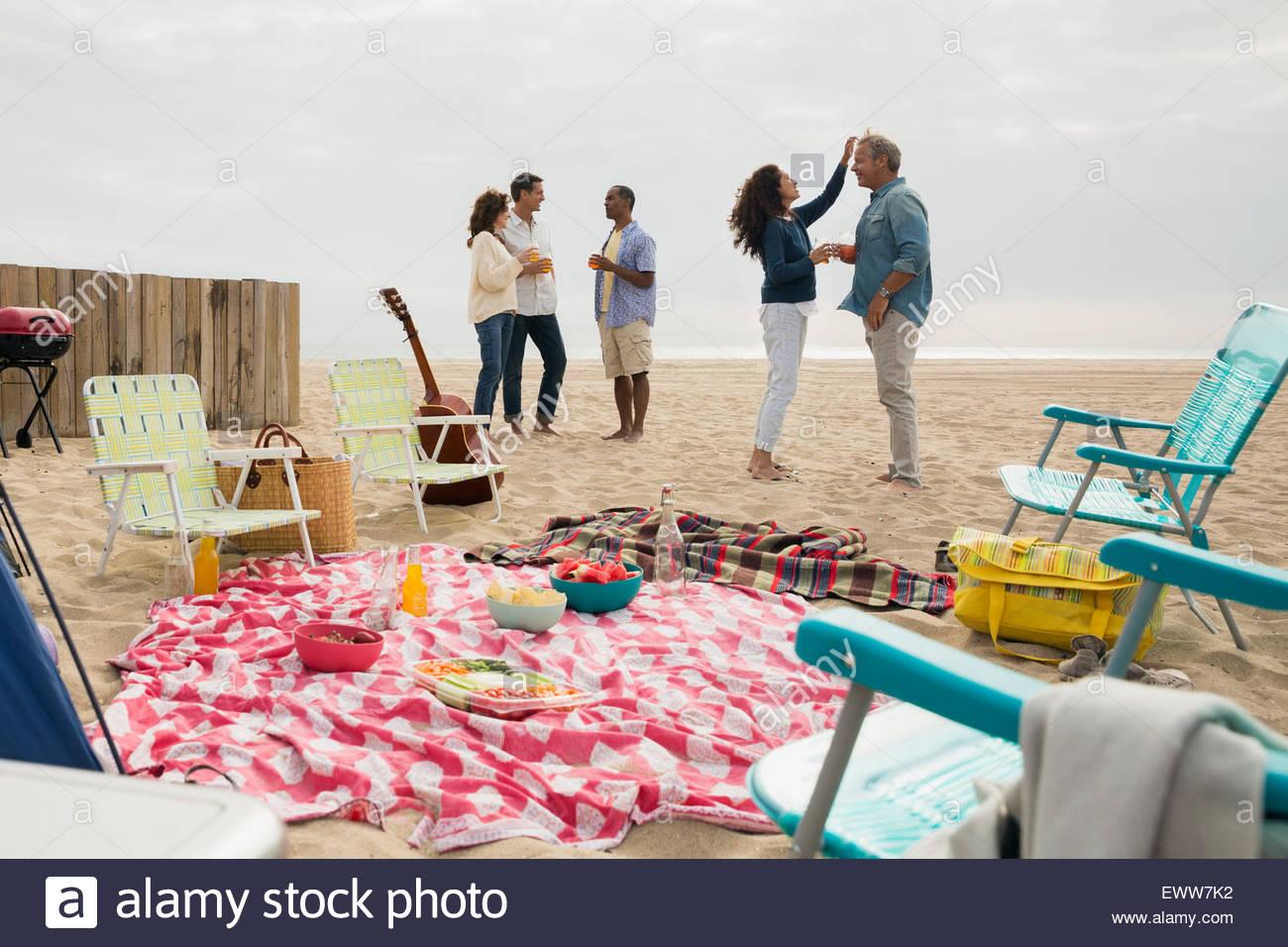 Friends enjoying beach picnic - Stock Image