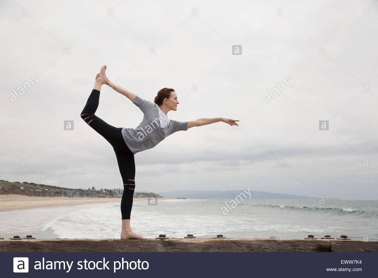 Woman doing yoga king dancer pose on beach - Stock Image