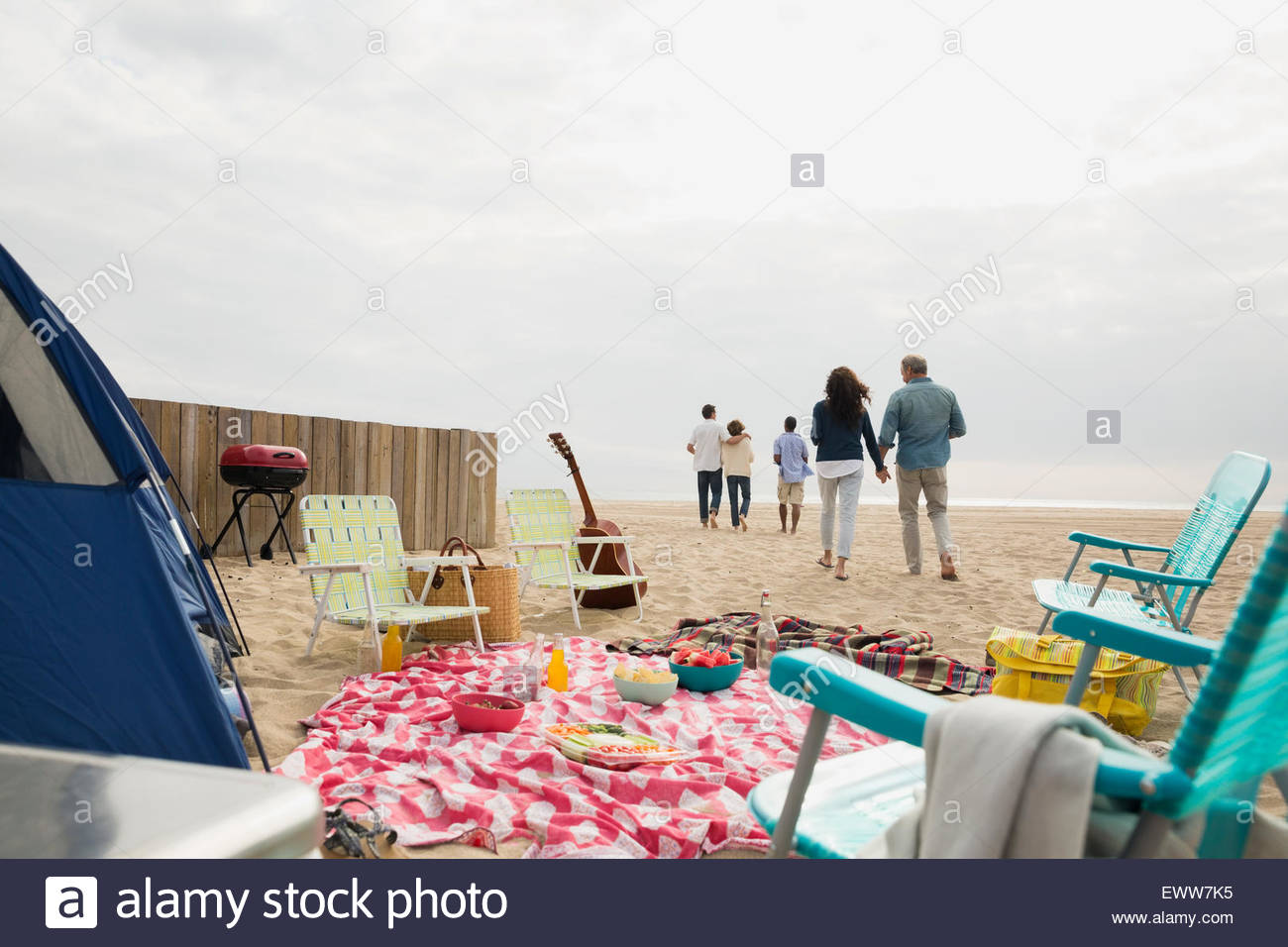 Friends walking away from beach picnic - Stock Image