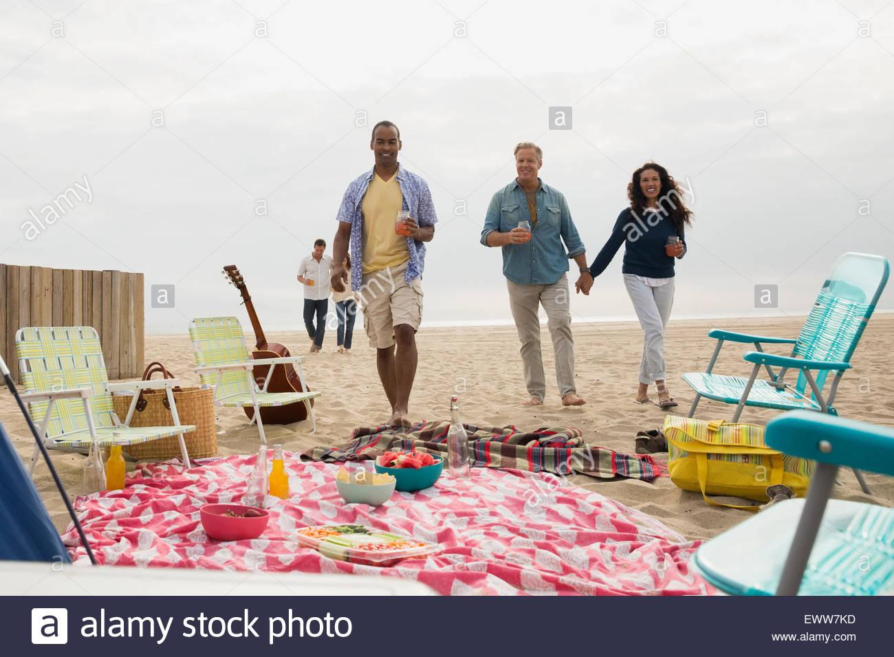 Friends walking toward beach picnic - Stock Image