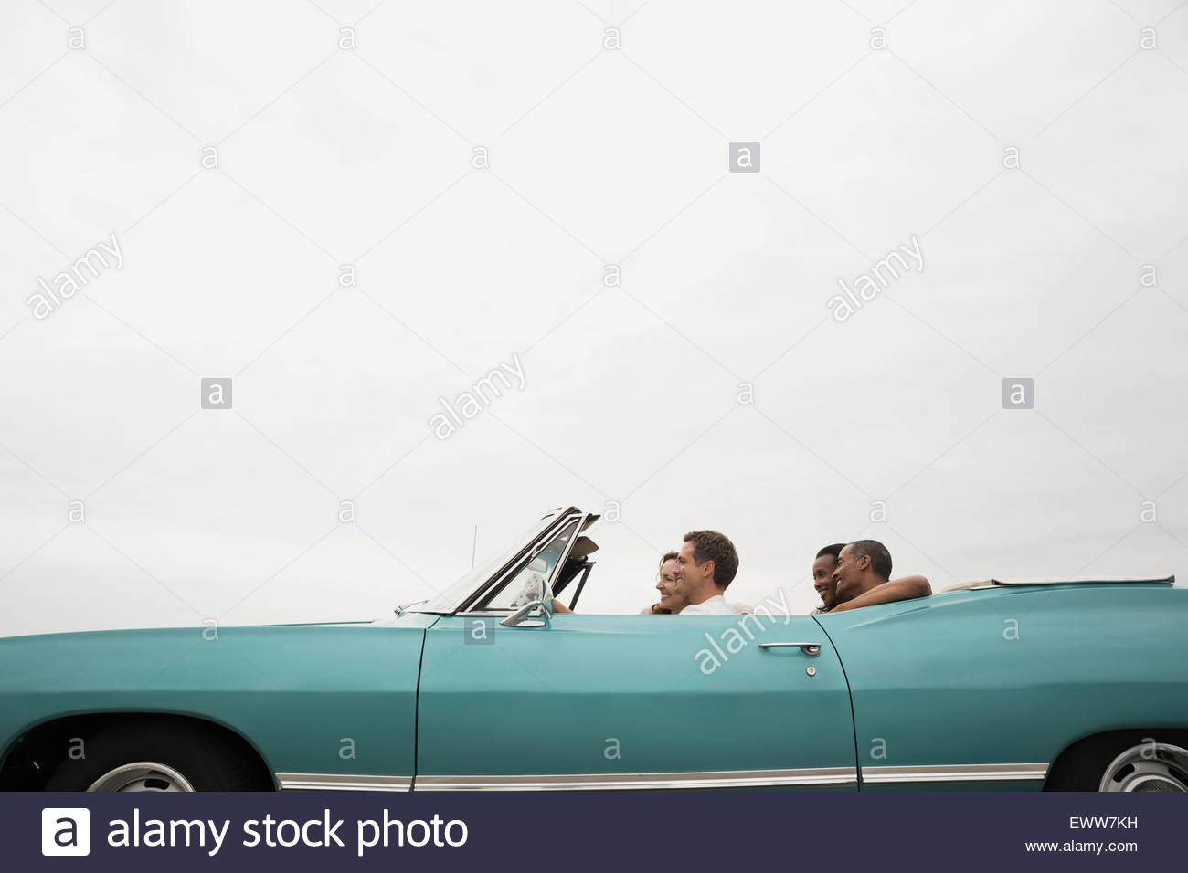 Couples riding in convertible under overcast sky Stock Photo