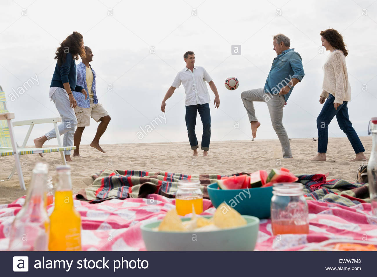 Friends playing soccer near beach picnic - Stock Image