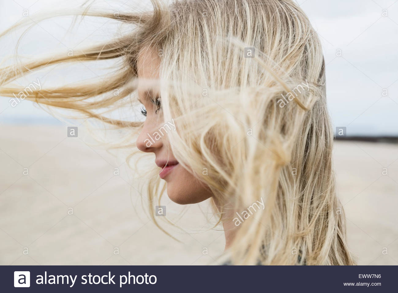 Wind blowing blonde hair of woman at beach - Stock Image