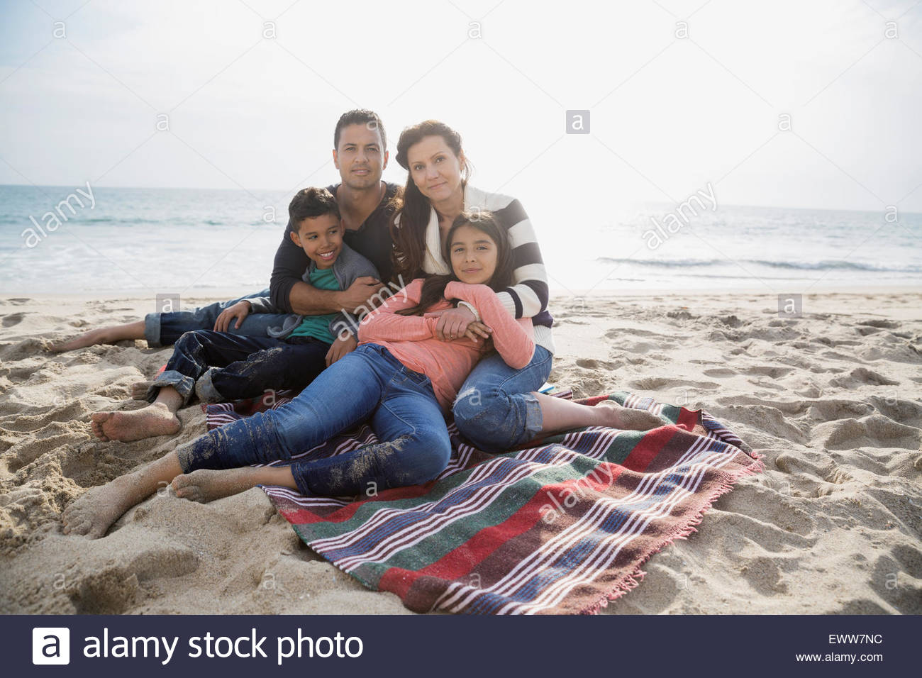 Portrait family relaxing on blanket on sunny beach - Stock Image