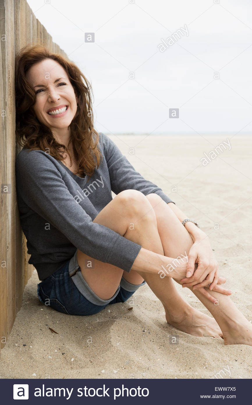 Portrait enthusiastic brunette woman sitting at beach wall Stock Photo