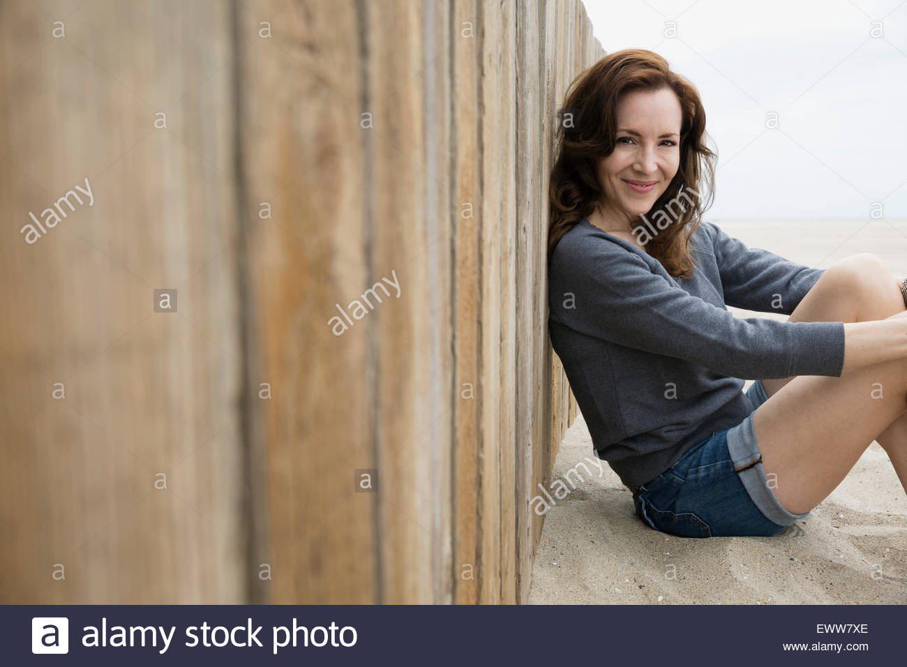Portrait smiling brunette woman sitting at beach wall - Stock Image