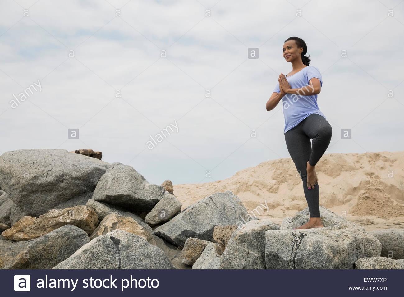 Woman in yoga tree pose on beach rocks - Stock Image