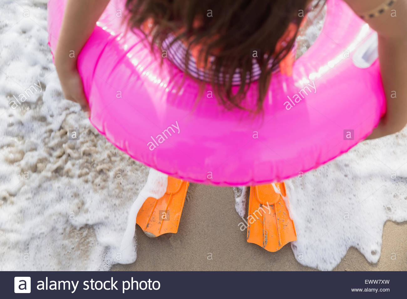 Girl in inflatable ring and flippers ocean surf - Stock Image