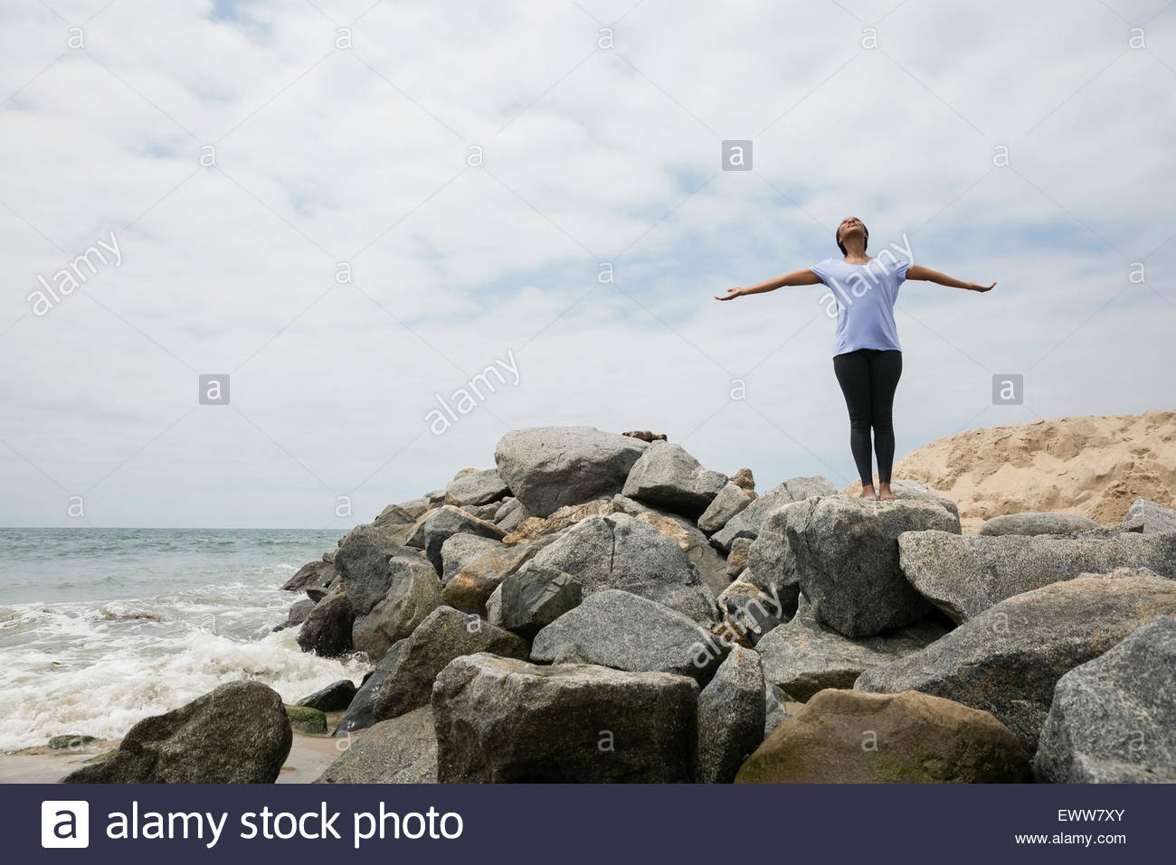 Woman doing yoga with arms outstretched beach rocks - Stock Image