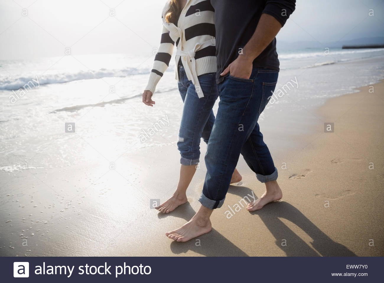 Barefoot couple walking on sunny beach - Stock Image