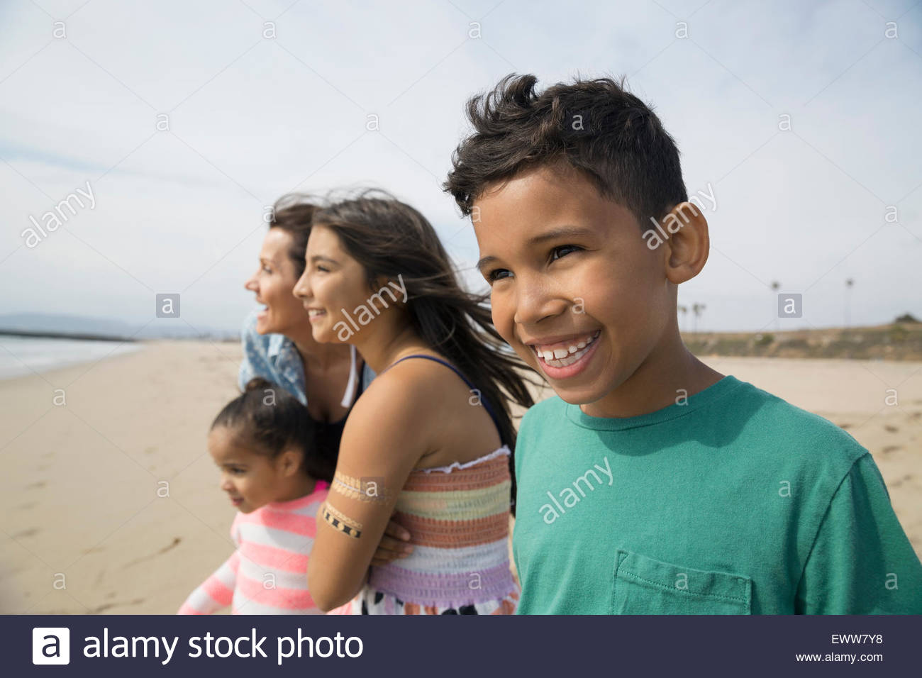 Smiling family looking at view from sunny beach - Stock Image