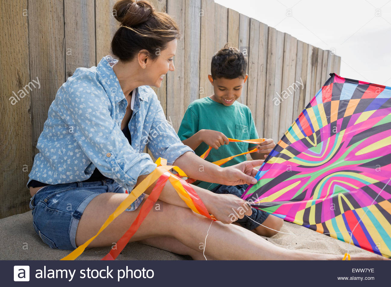 Mother and son preparing to fly kite at beach - Stock Image