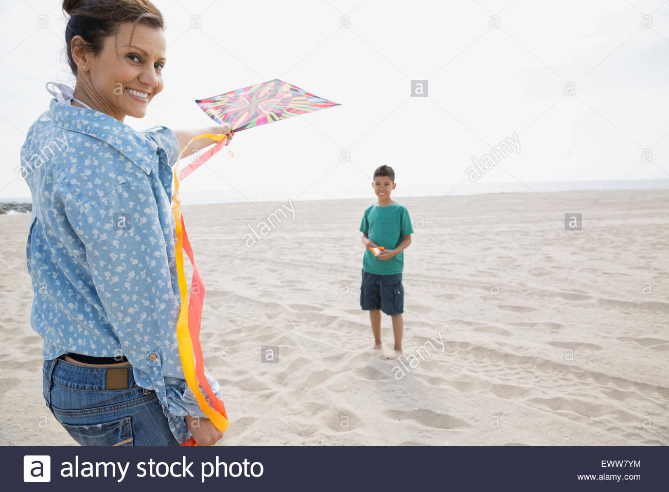 Portrait mother and son flying kite at beach - Stock Image