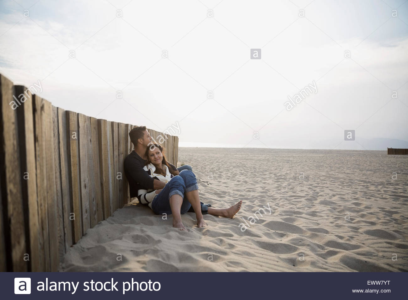 Affectionate couple relaxing at beach wall - Stock Image