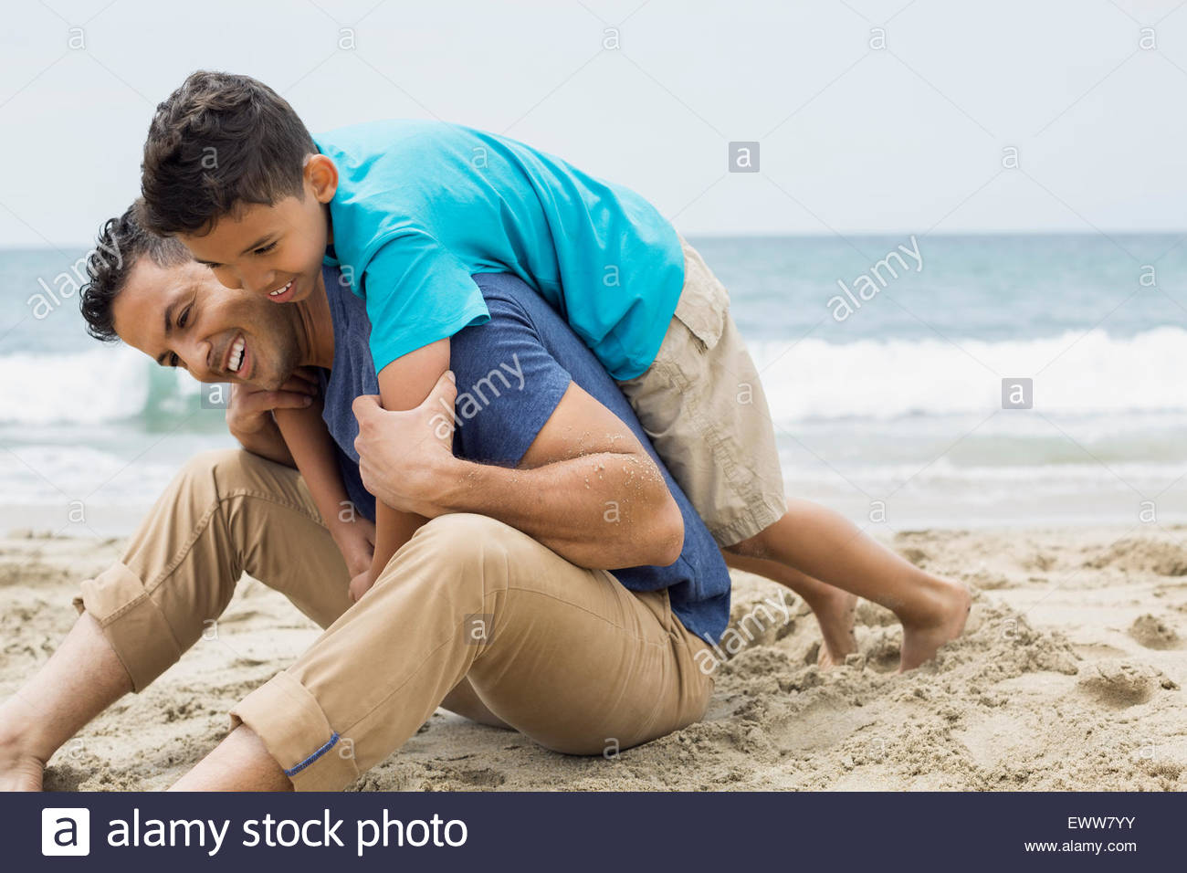 Playful father and son hugging on beach - Stock Image
