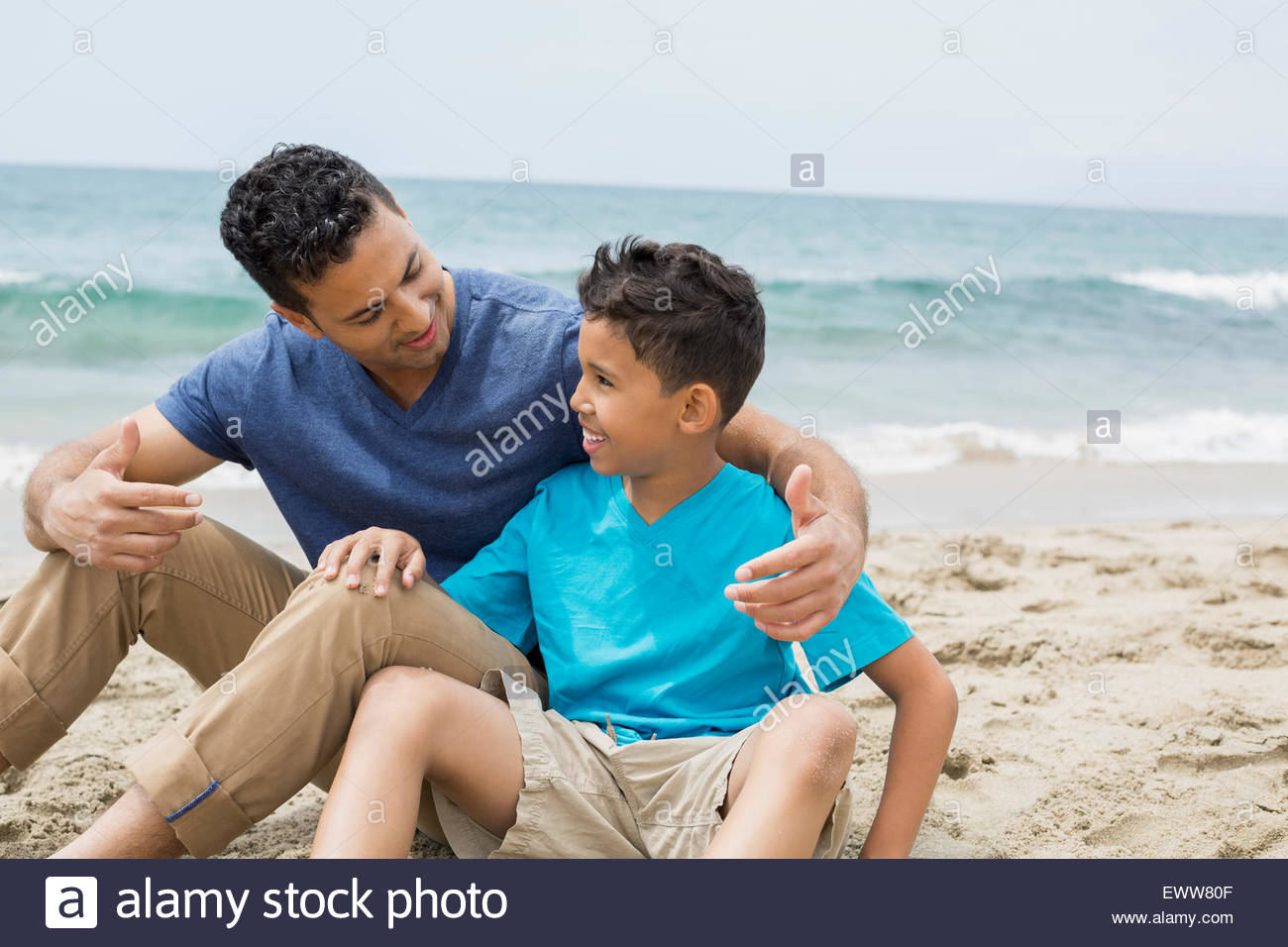 Father and son hugging on beach - Stock Image