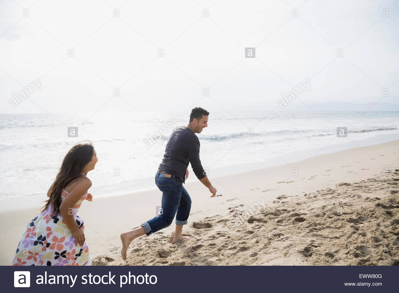 Daughter running and chasing father on sunny beach - Stock Image