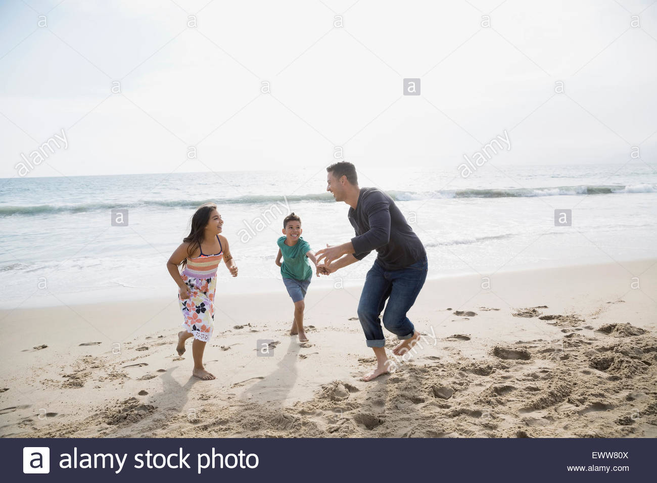 Playful family running on sunny beach - Stock Image