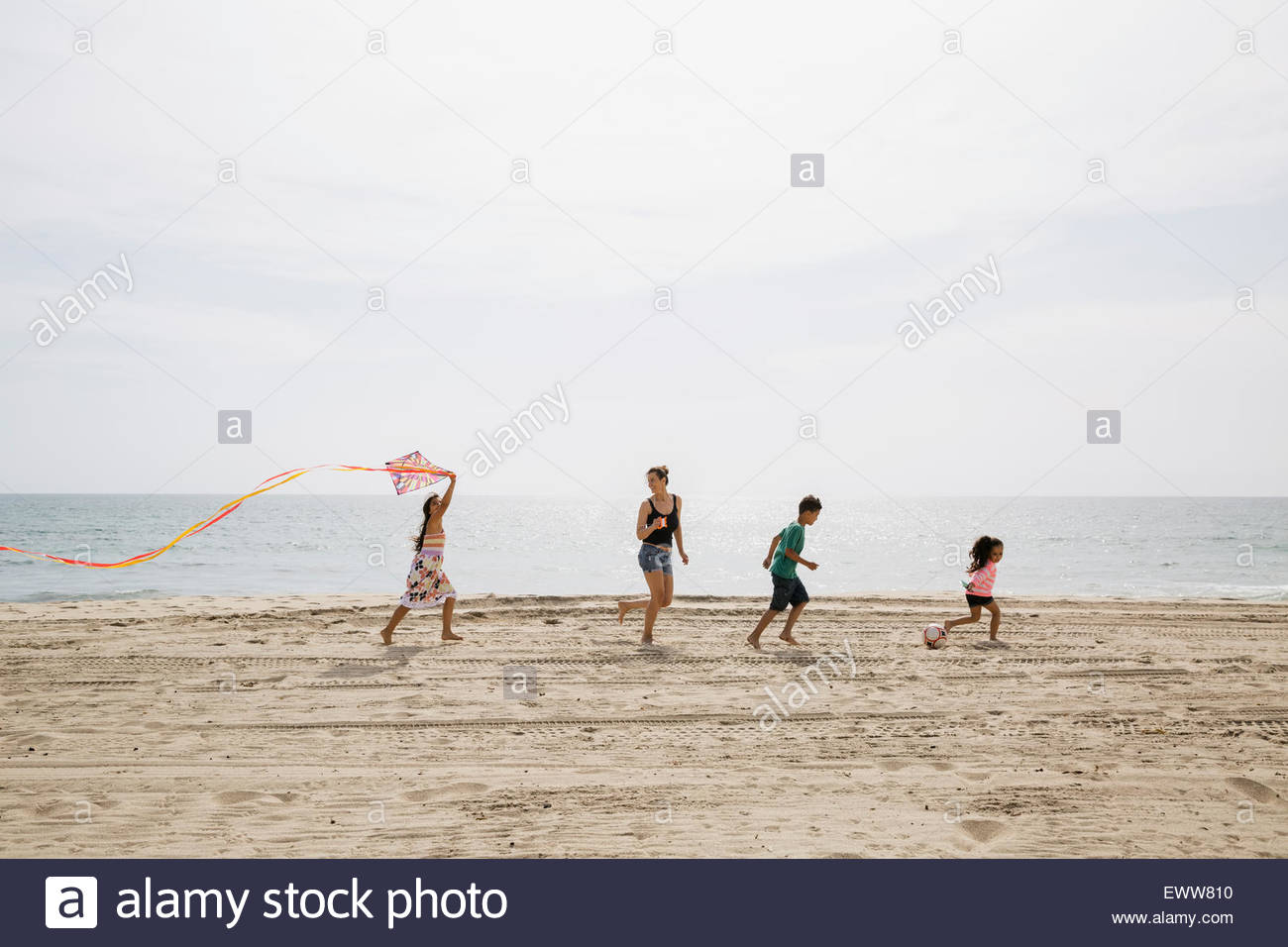 Family flying kite on sunny beach - Stock Image