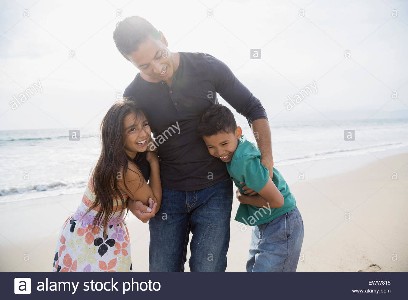 Portrait family hugging on sunny beach - Stock Image