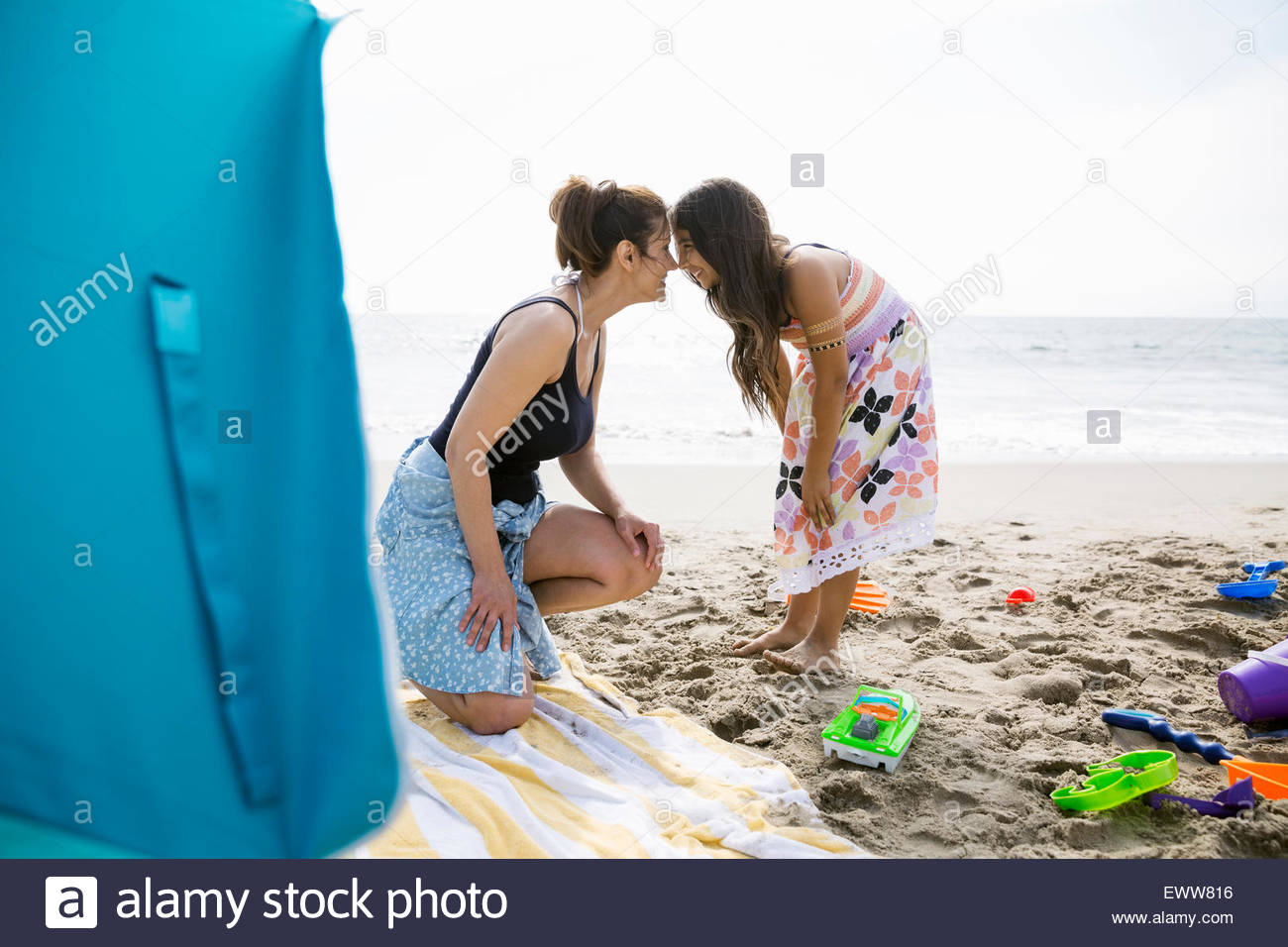 Affectionate mother and daughter rubbing noses sunny beach - Stock Image