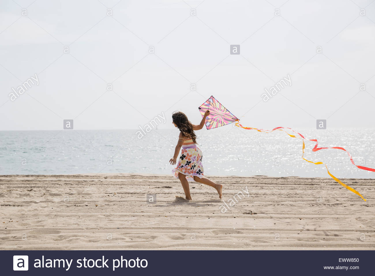 Girl flying kite on sunny beach - Stock Image