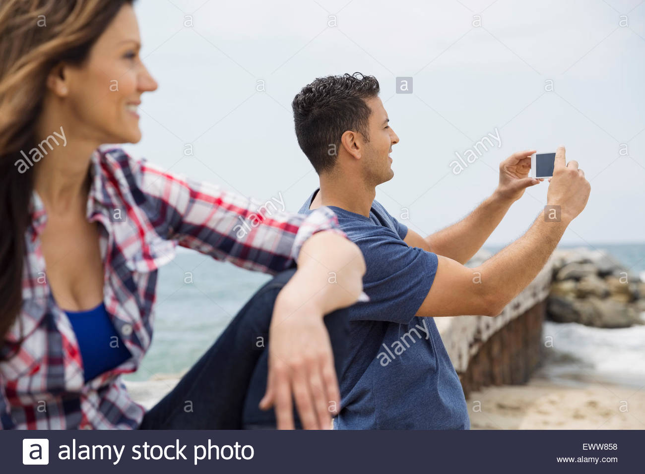 Man photographing with camera phone at beach Stock Photo