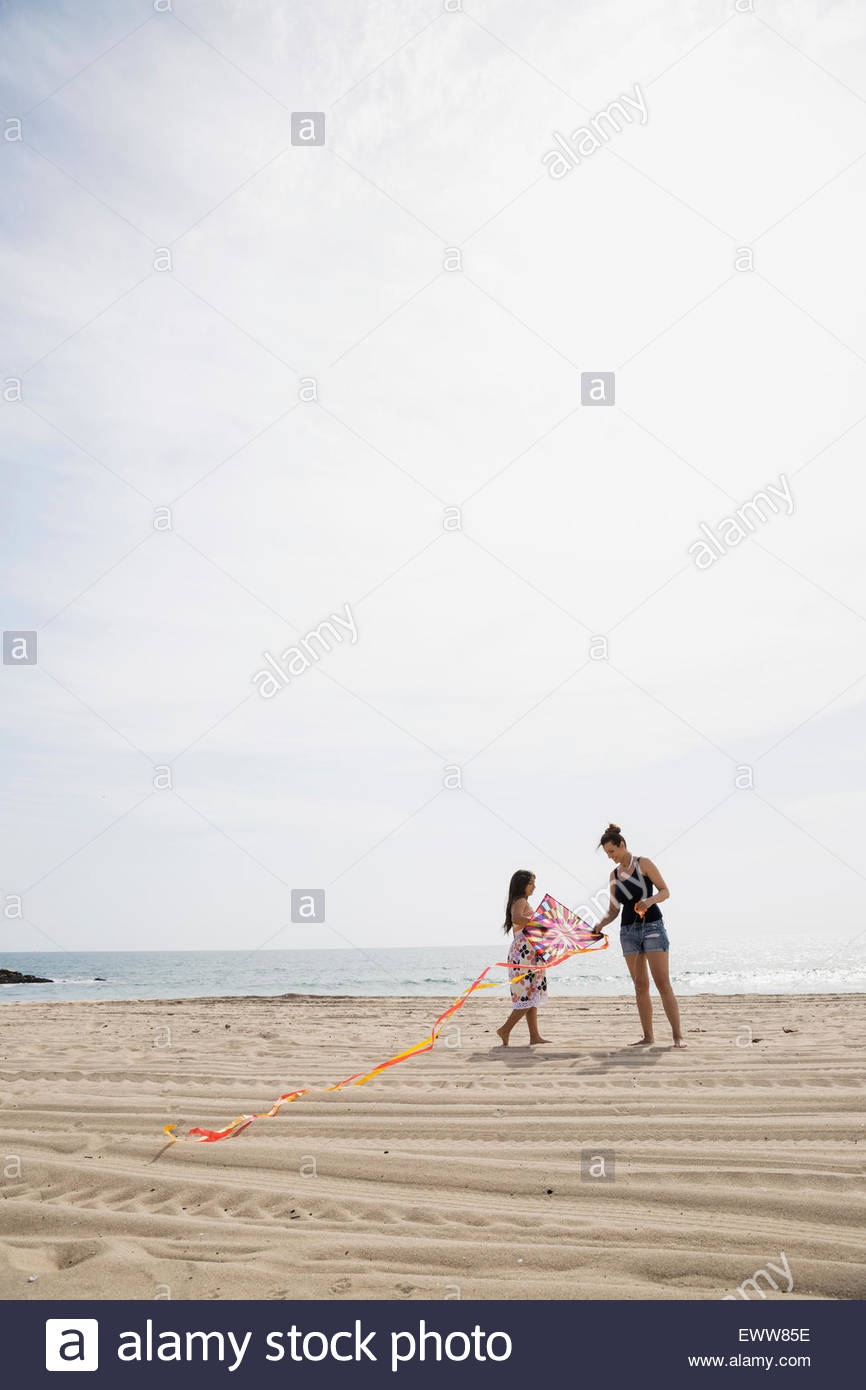 Mother and daughter preparing fly kite sunny beach - Stock Image