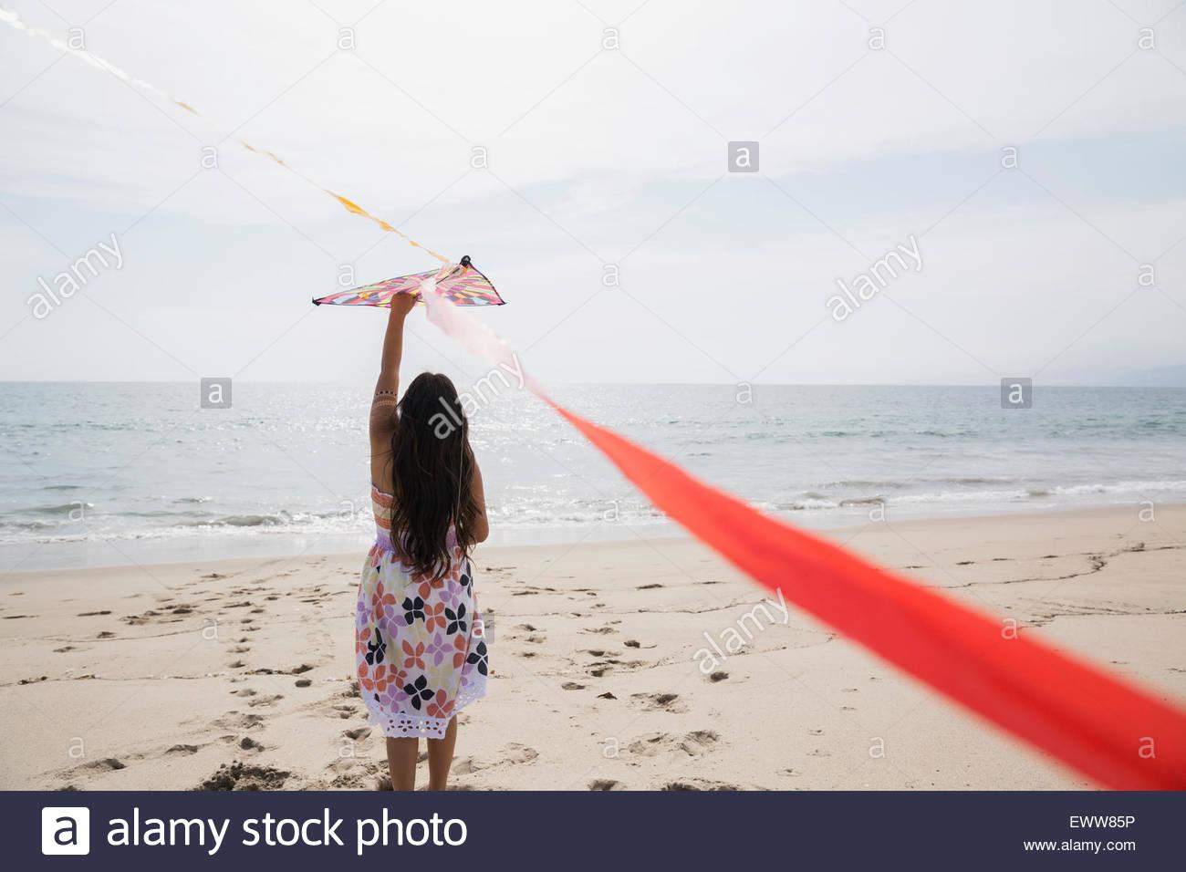 Girl in dress flying kite on sunny beach - Stock Image