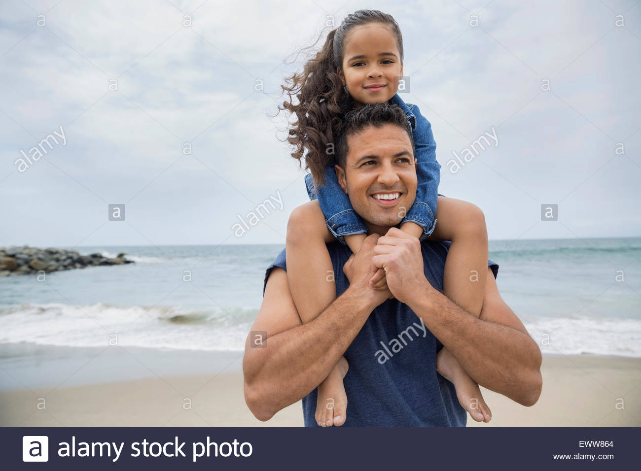 Portrait father carrying daughter on shoulders at beach - Stock Image