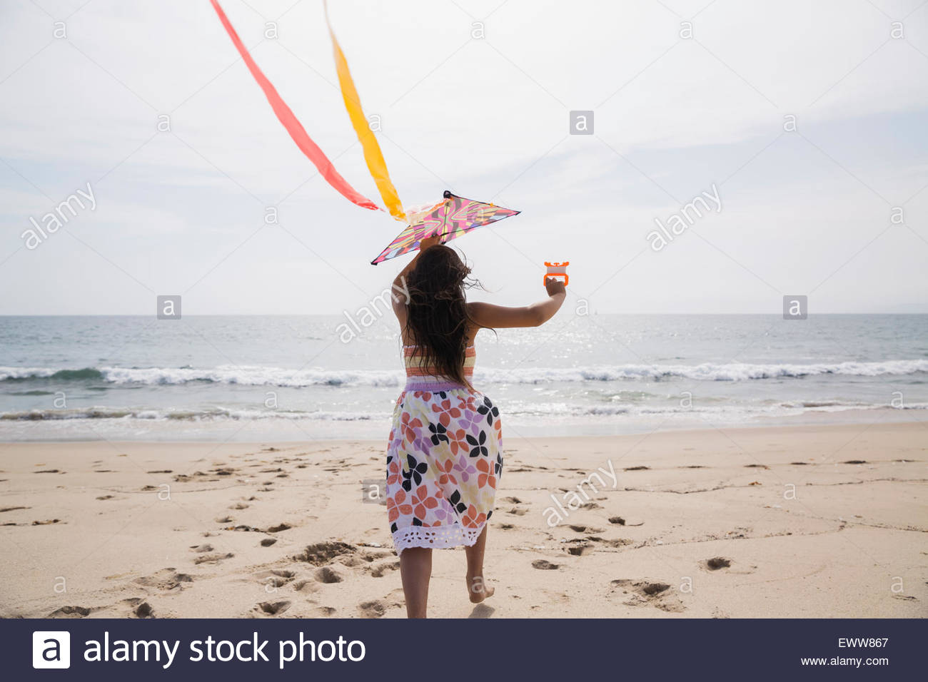 Girl in dress flying kite on sunny beach - Stock Image