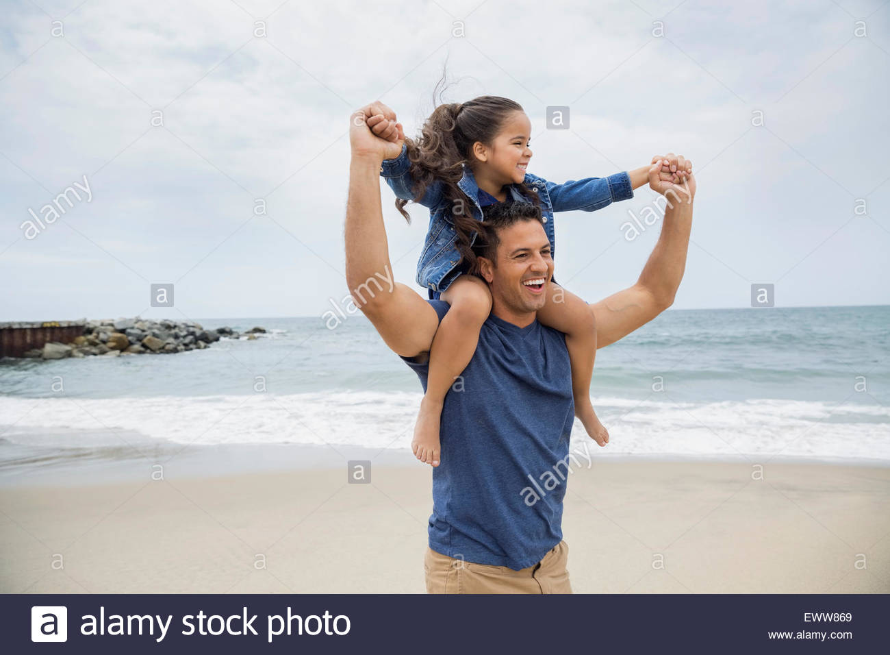 Playful father carrying daughter on shoulders at beach - Stock Image