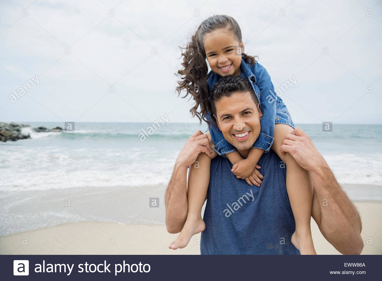 Portrait smiling father carrying daughter on shoulders beach - Stock Image