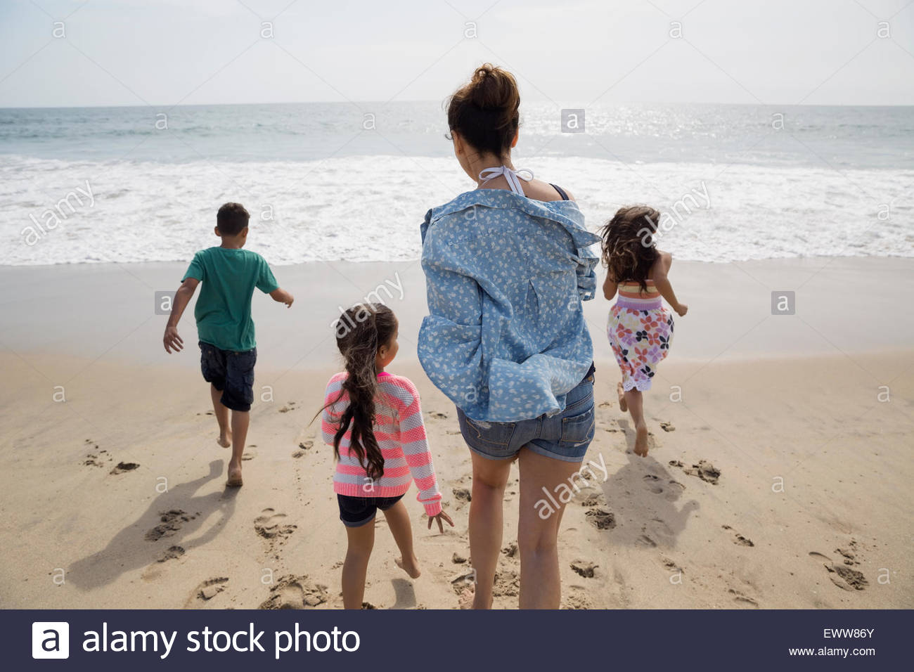 Family running toward ocean on sunny beach Stock Photo
