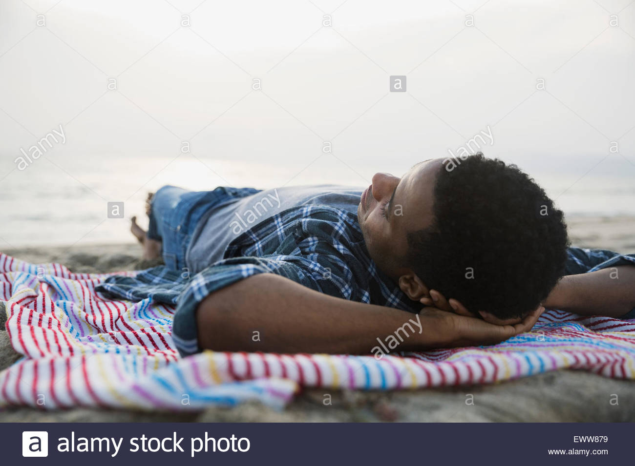 Serene man sleeping on beach blanket - Stock Image
