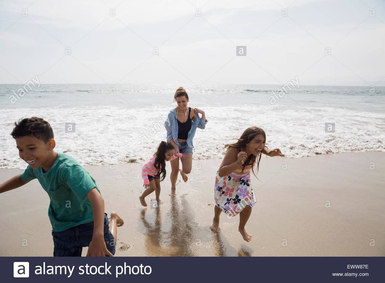 Family running from ocean onto sunny beach - Stock Image