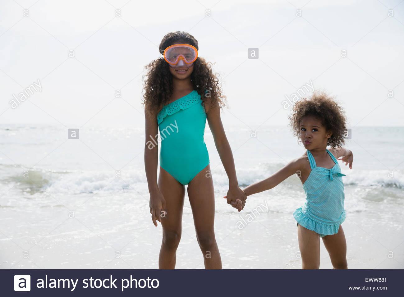 Portrait sisters in bathing suits wading in ocean - Stock Image