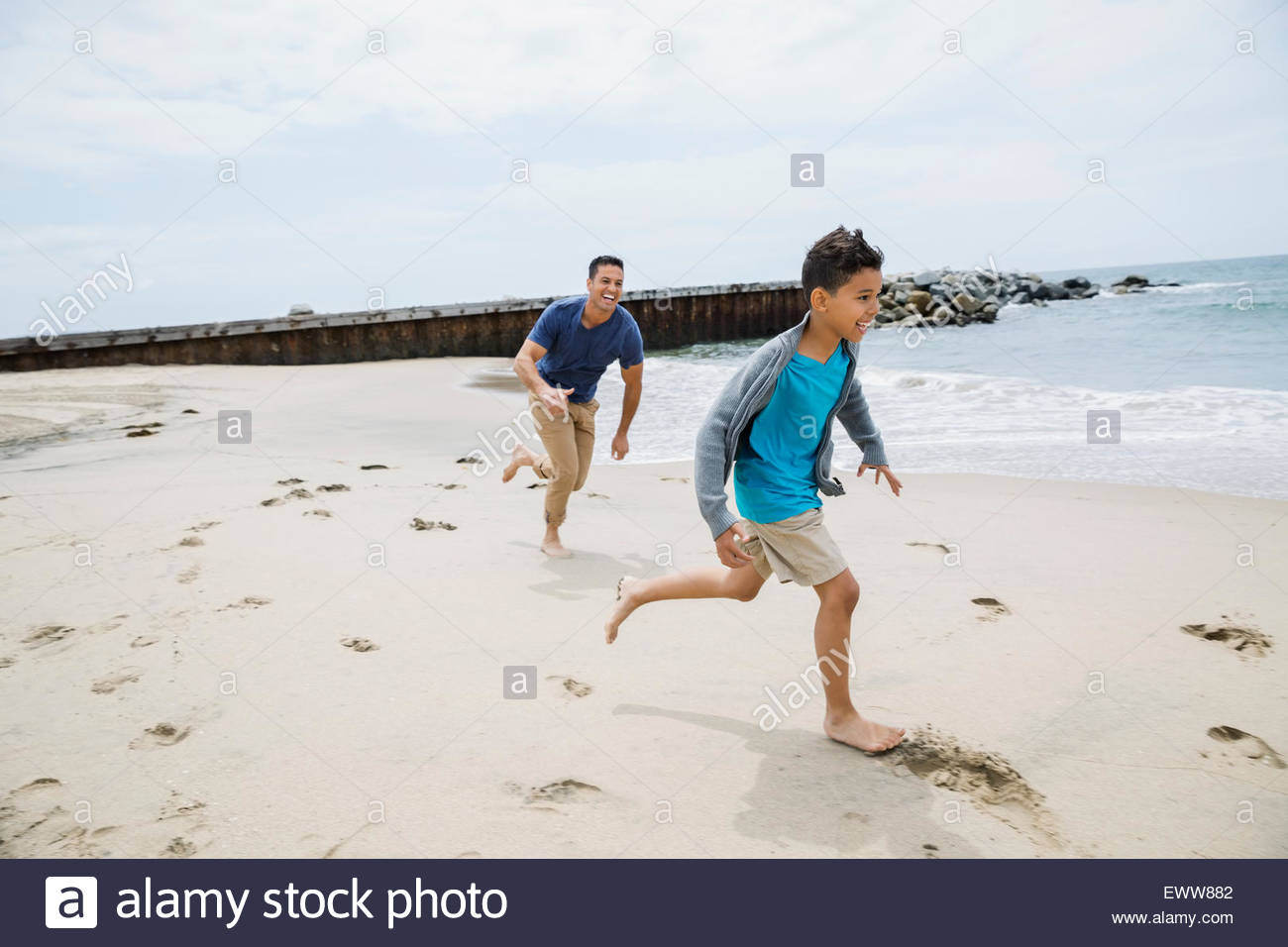 Father running and chasing son on sunny beach - Stock Image