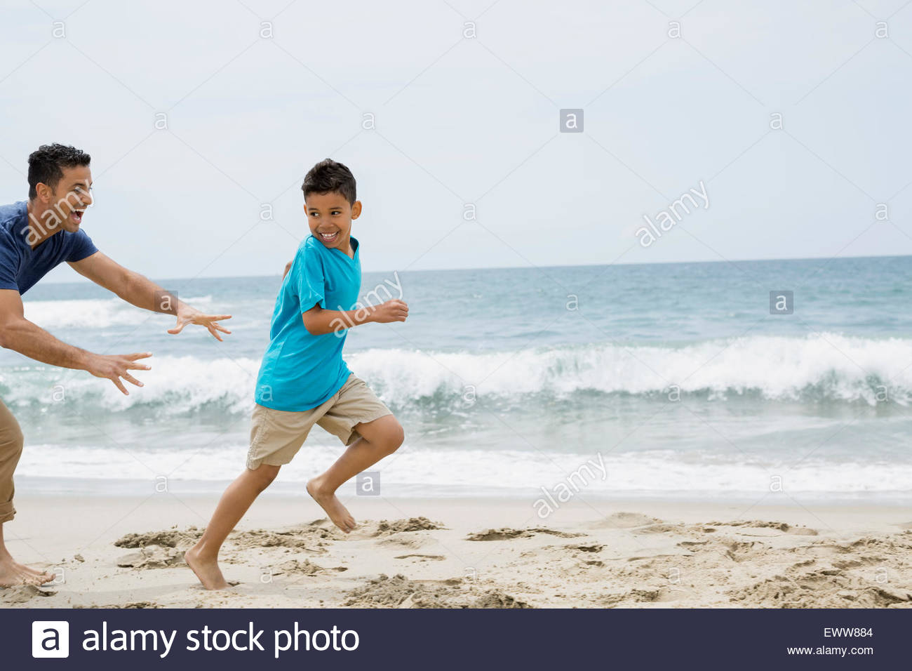 Father running and chasing son on beach - Stock Image