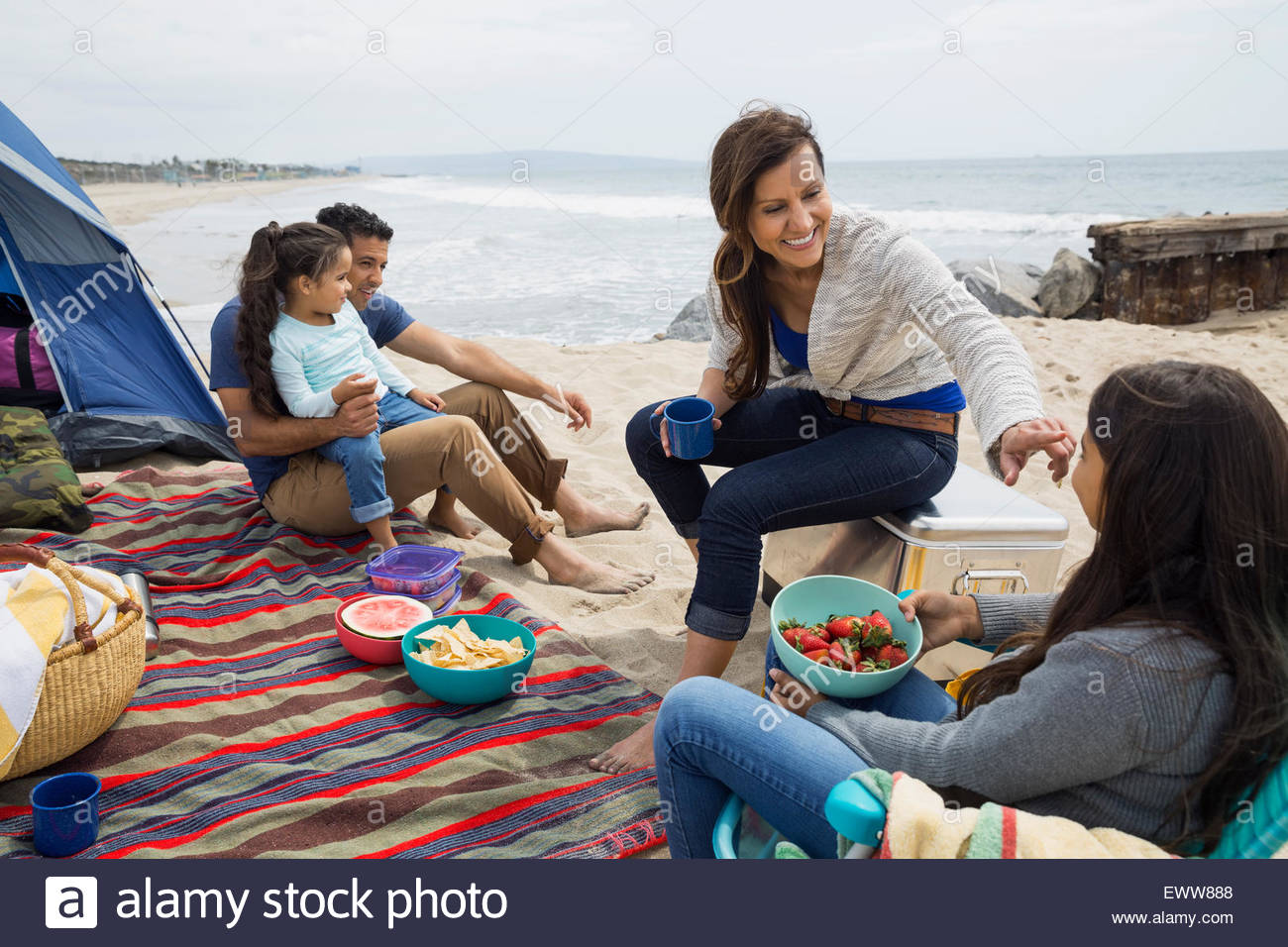 Family picnicking outside tent on beach Stock Photo
