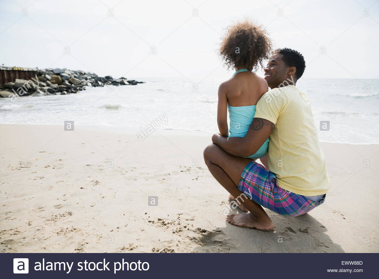 Father and daughter looking at ocean from beach - Stock Image