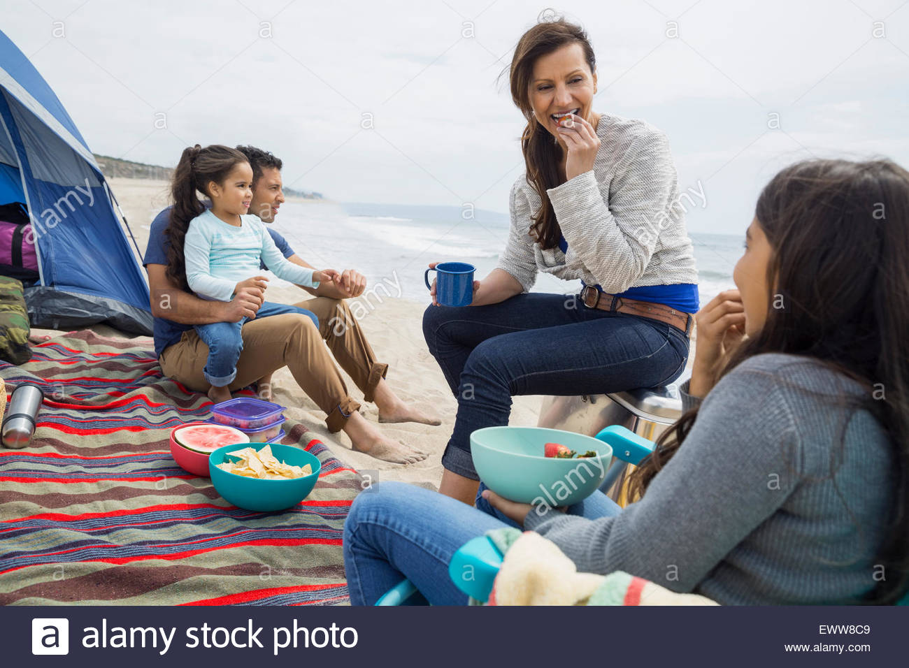 Family picnicking outside tent on beach - Stock Image