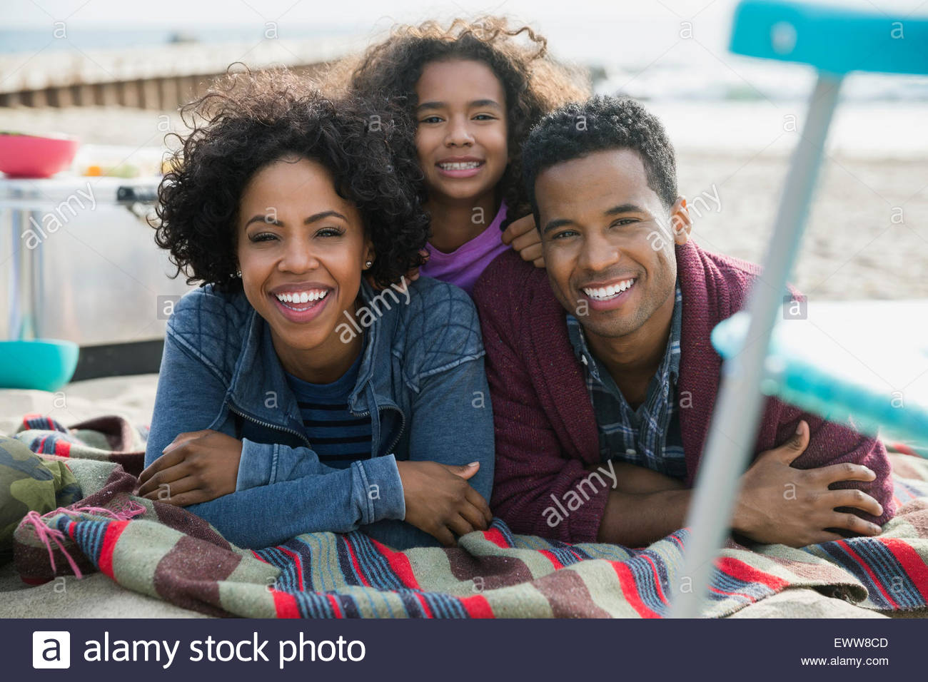 Portrait smiling family laying on beach - Stock Image