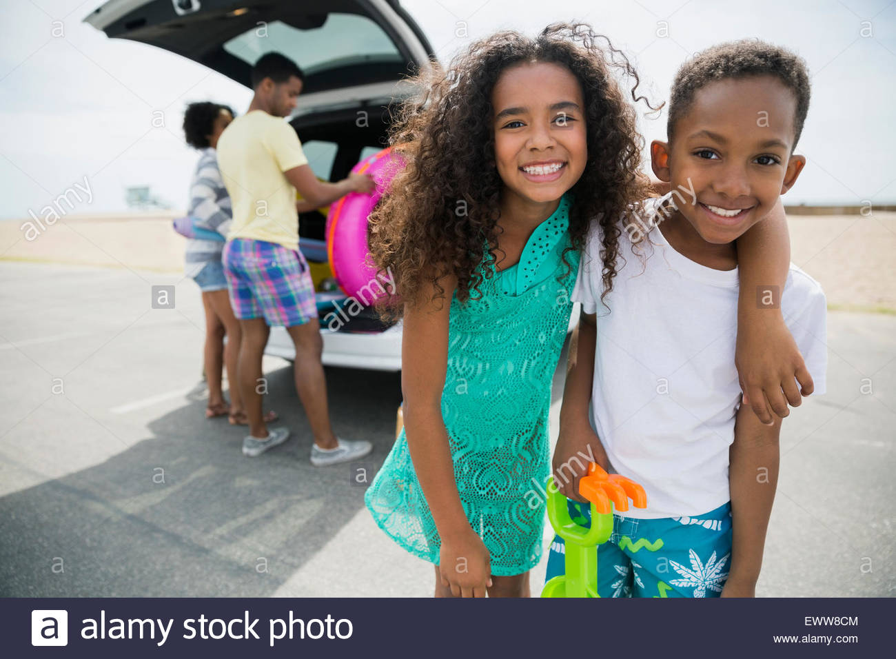 Portrait enthusiastic brother and sister arriving at beach - Stock Image