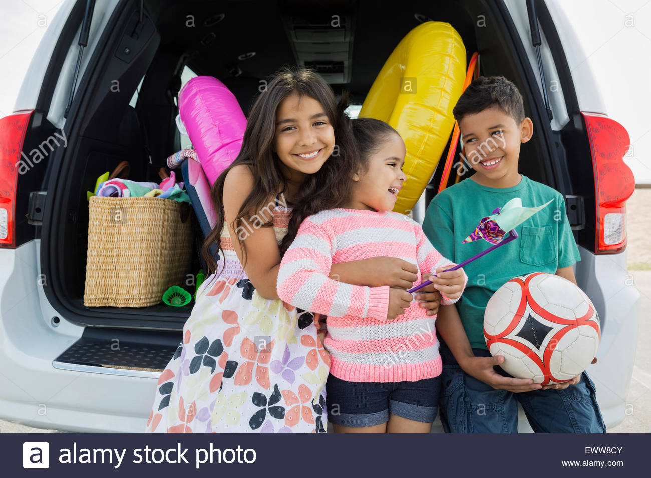 Portrait brother and sisters van arriving at beach - Stock Image