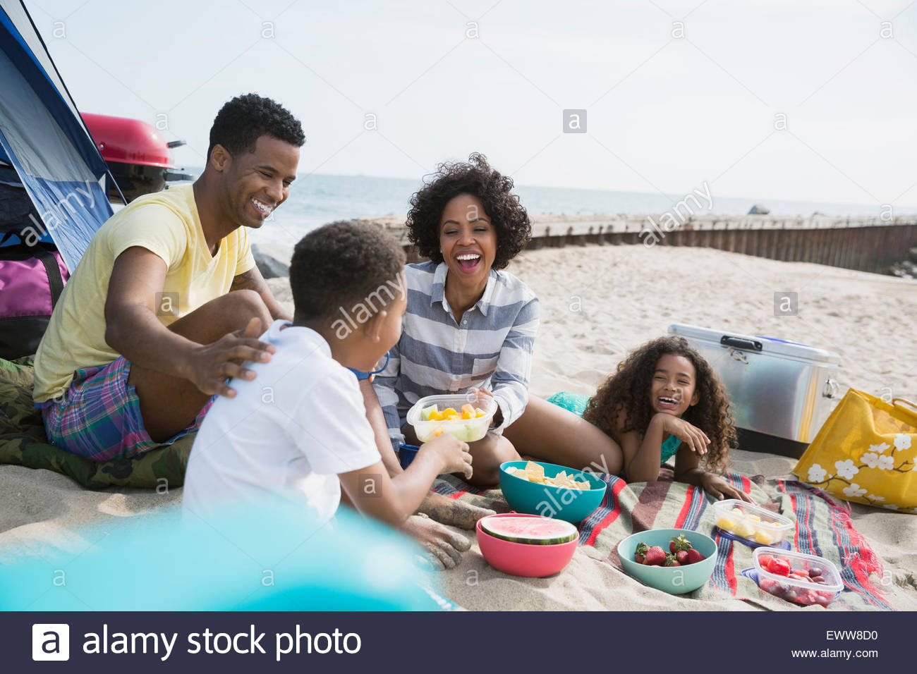 Family picnicking on beach - Stock Image
