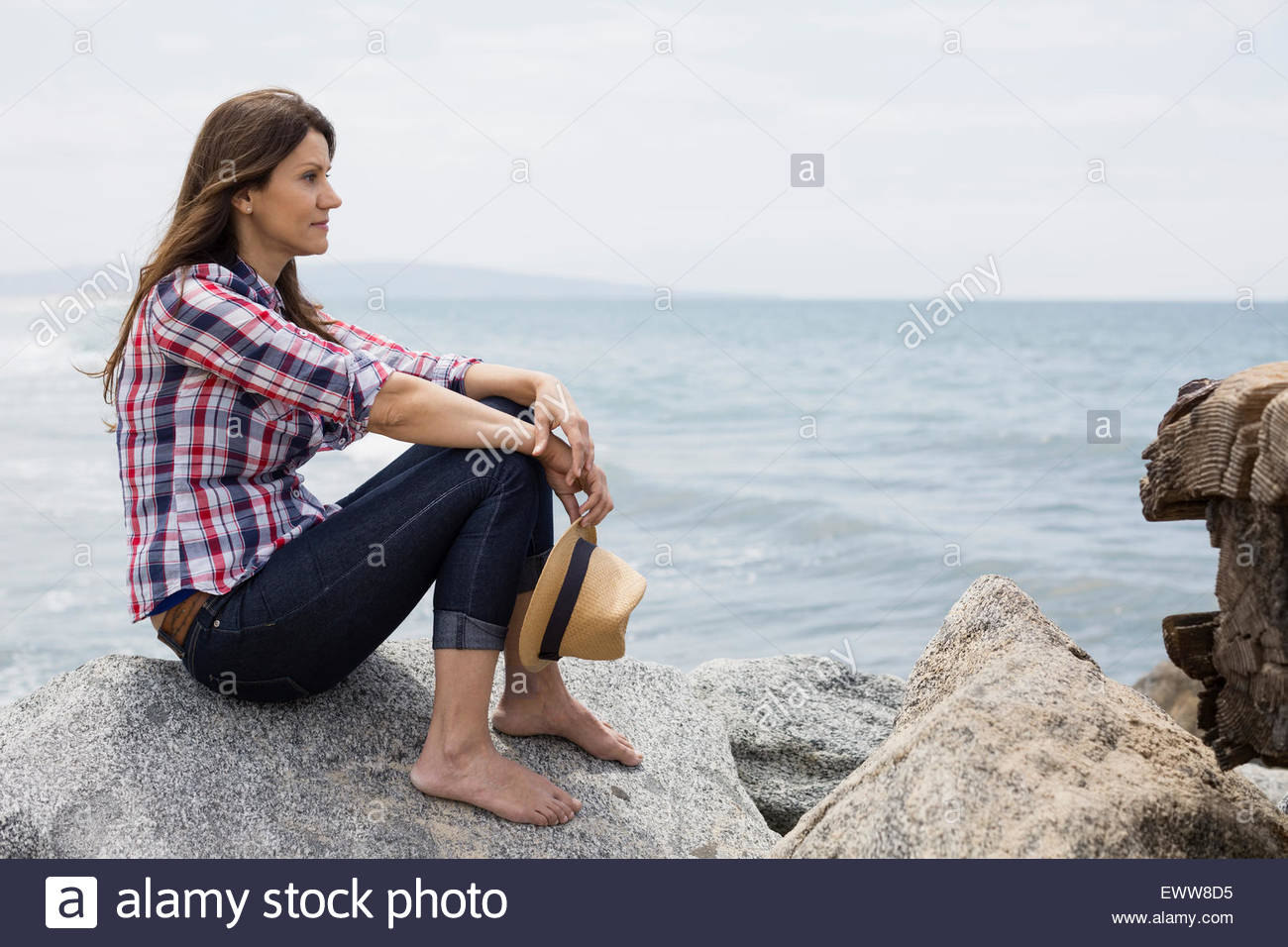 Pensive barefoot woman sitting on rocks at ocean - Stock Image
