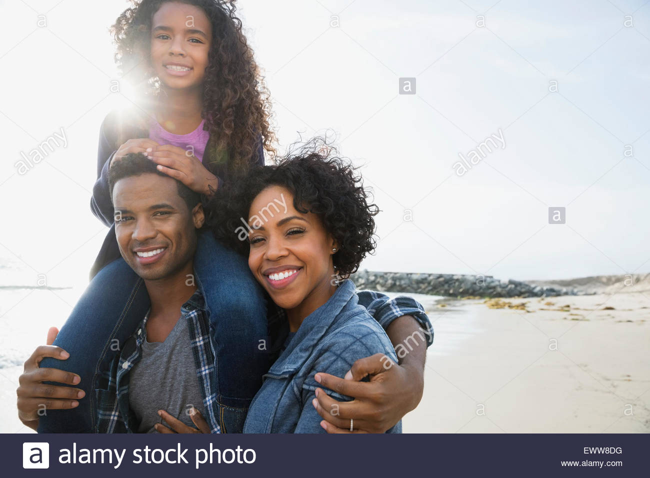 Portrait smiling family on sunny beach - Stock Image